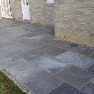 Decorative garden patio in grey stone slabs