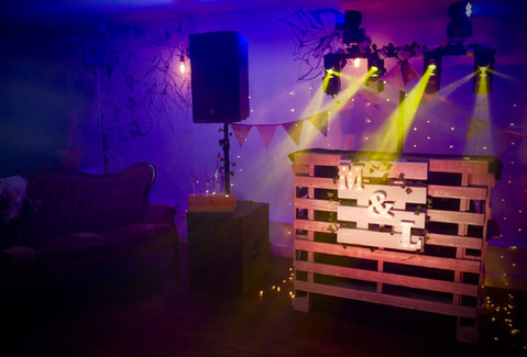 Tasteful disco lighting with rustic bespoke wedding dj booth made from pallets with personalised handmade illuminated initails letters sign in Bristol and Somerset