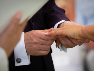 Groom putting ring on bride's finger during ceremony