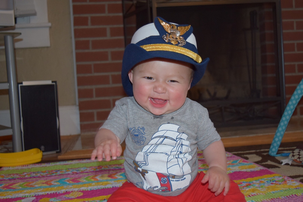 Adorable baby smiling and wearing his mom's Coast Guard cap