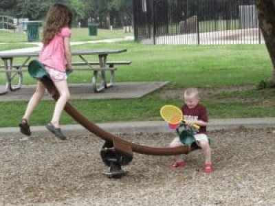 Quatro and Cinco Lee playing on teeter totter
