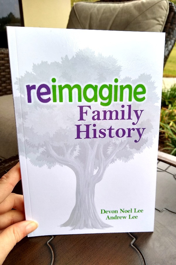 Hand holding a copy of the book Reimagine Family History Book