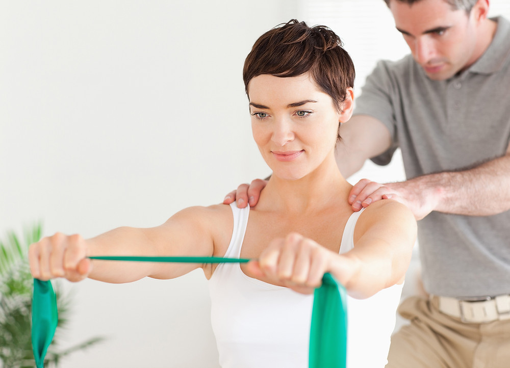 physiotherapist showing exercises for a patient with shoulder instability