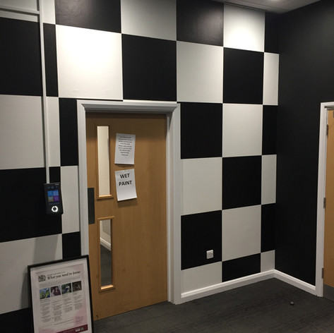 Walls painted in black and wallpapered