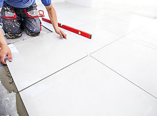 Laying tiles at home. Construction worke