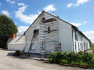 Man on scaffolds painting a house during