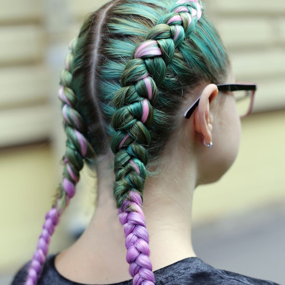 A lady with green and pink platted hairstyle