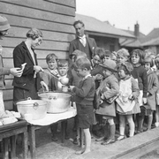 Schoolchildren line up for free issue of soup and a slice of bread during the Depression