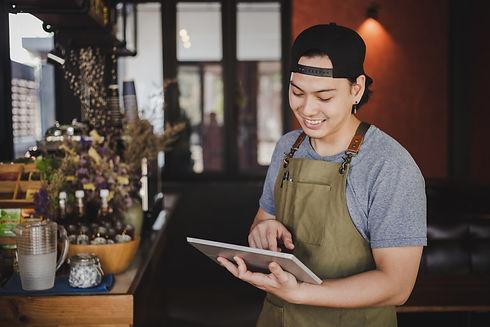 asian-man-barista-holding-tablet-checkin