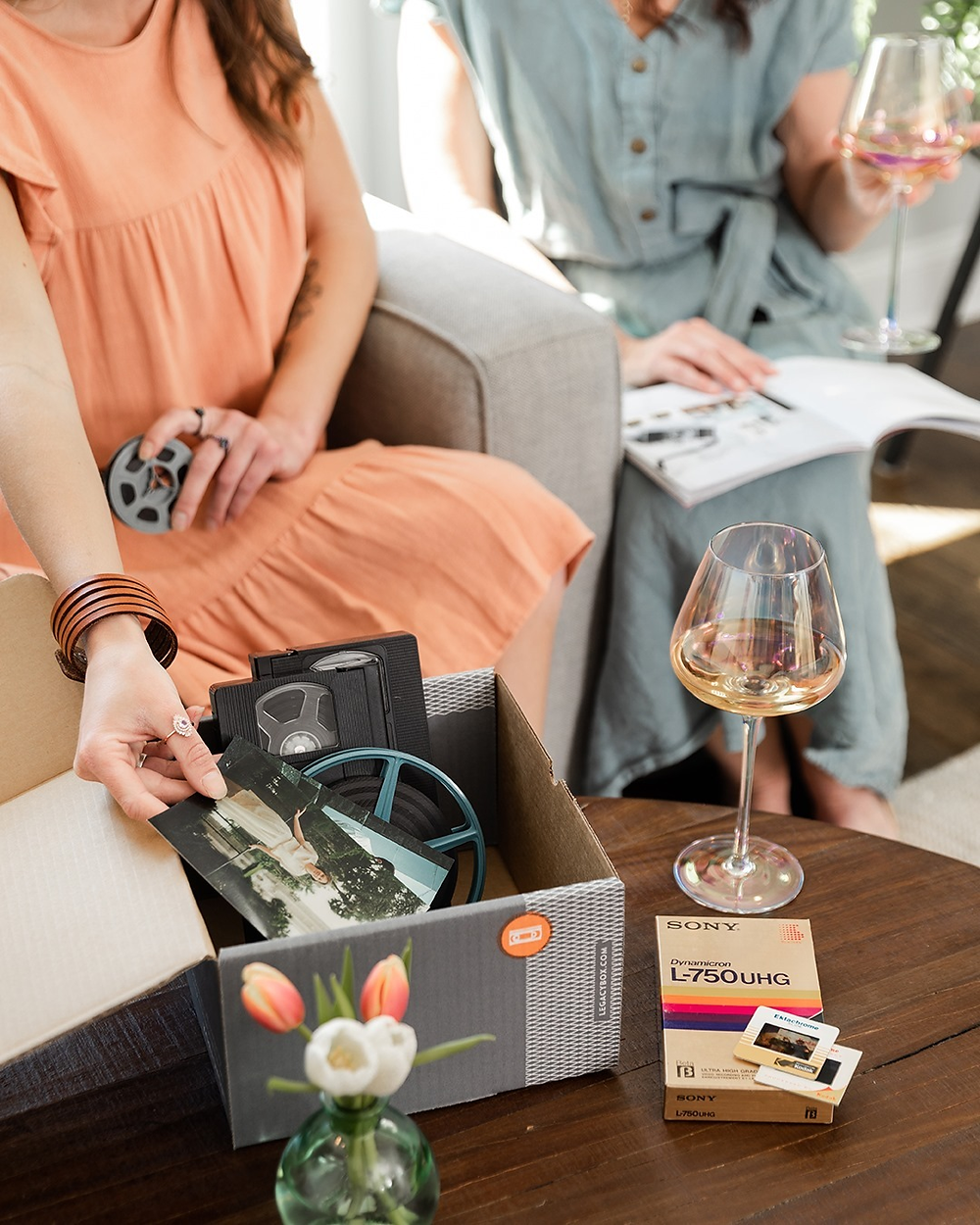 legacy box memory preservation kit with vhs on a table with a glass of wine