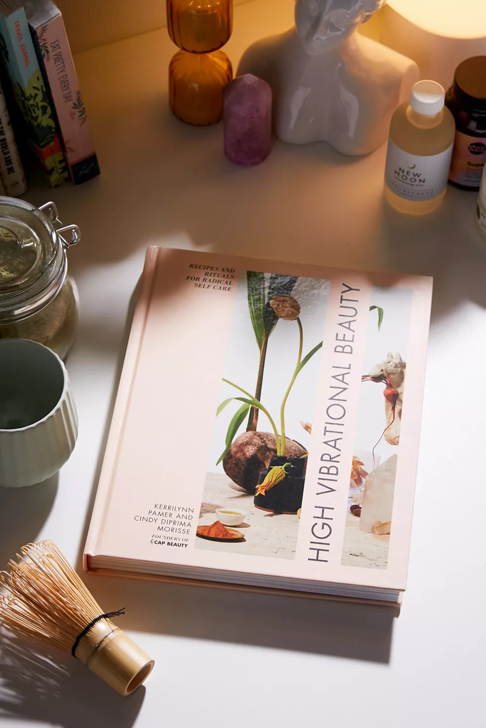 High Vibrational Beauty book on a table with a matcha whisk and crystals