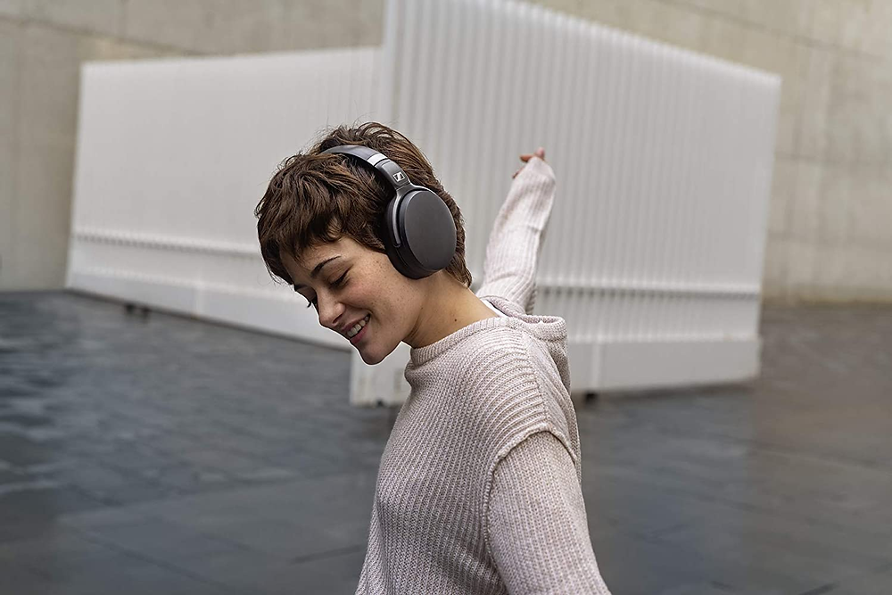 woman with short hair wearing over ear sennheiser headphones wearing white sweater and spreading arms sennheiser wireless over ear bluetooth headphones