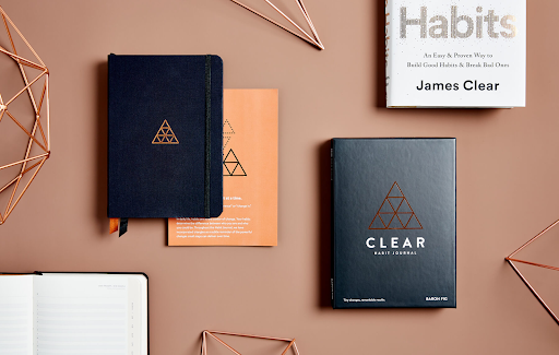 journals on an orange table james clear habit journal