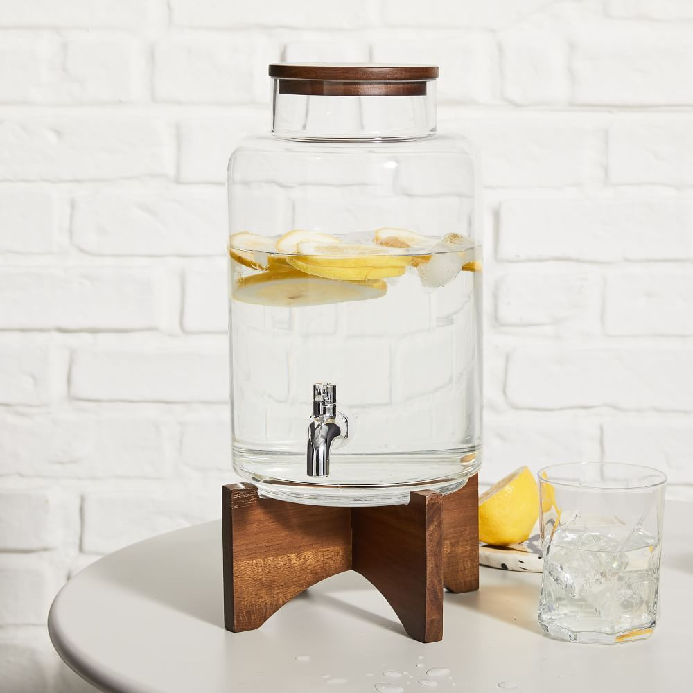 large glass water dispenser filled with water and lemon slices on a wooden base