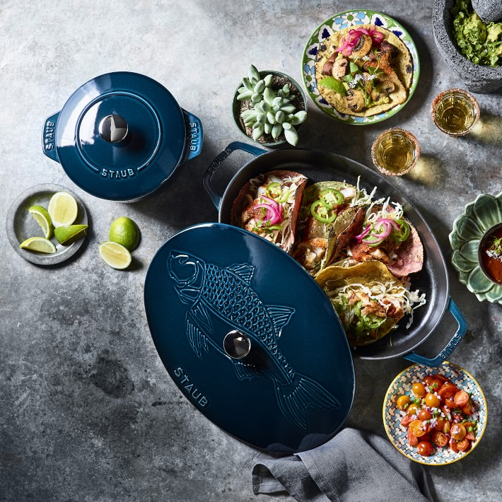 dark blue staub dutch oven partially open with tacos inside on a concrete table