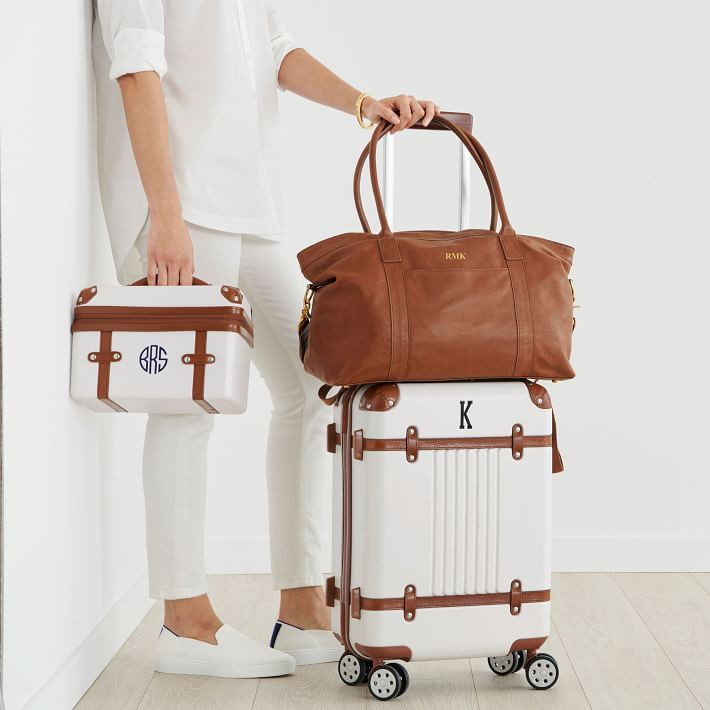 woman carrying monogrammed travel luggage business class