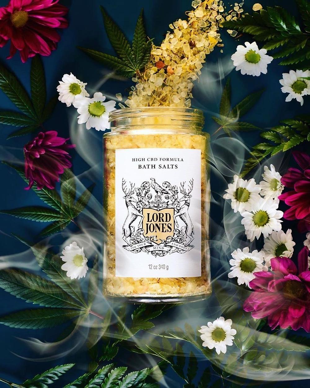 Lord Jones CBD bath salts in a background of flowers