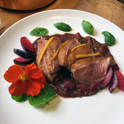 roasted duck on a wine sauce on a plate