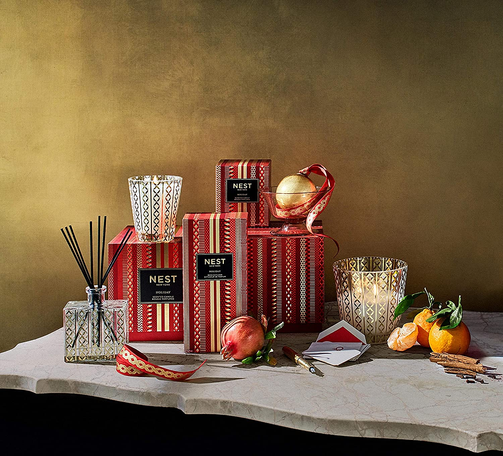 red boxes and a candle on a marble table with fruits