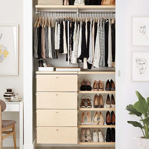 closet organized with shoe rack drawers and hangers above