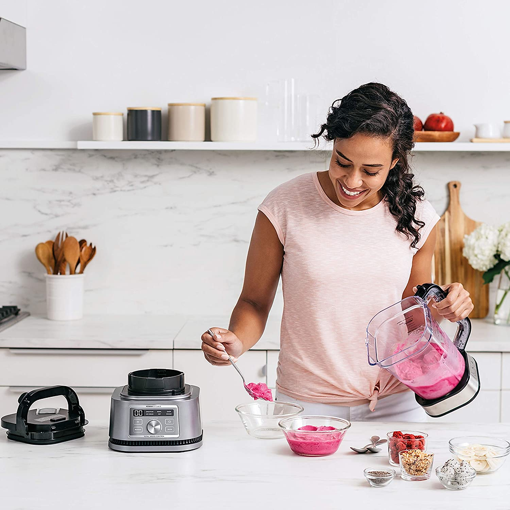 woman making a pink smoothie bowl using a ninja food processor