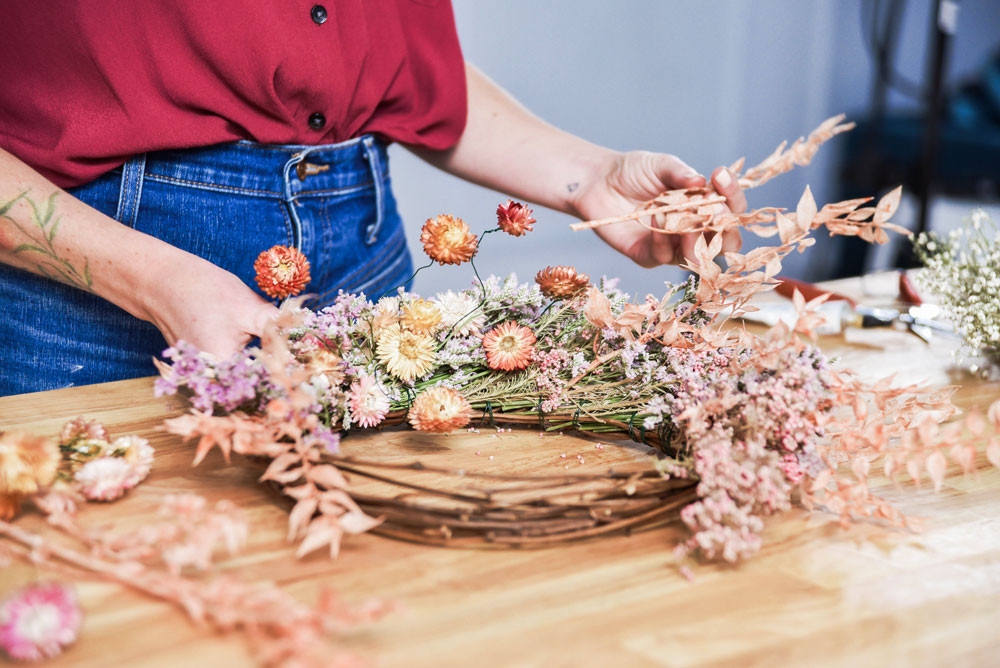 Woman putting together dried flower wreath