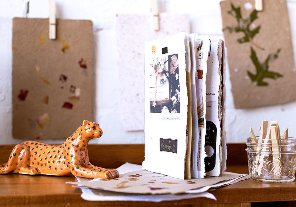 handmade paper pamphlet on a wood table with jaguar figurine