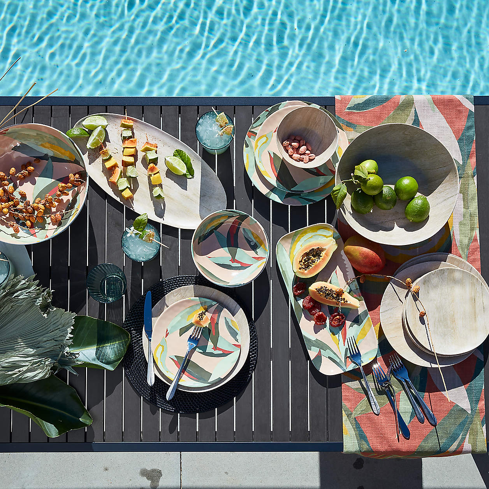 colorful outdoor dinner set with palm leaf design on a table poolside