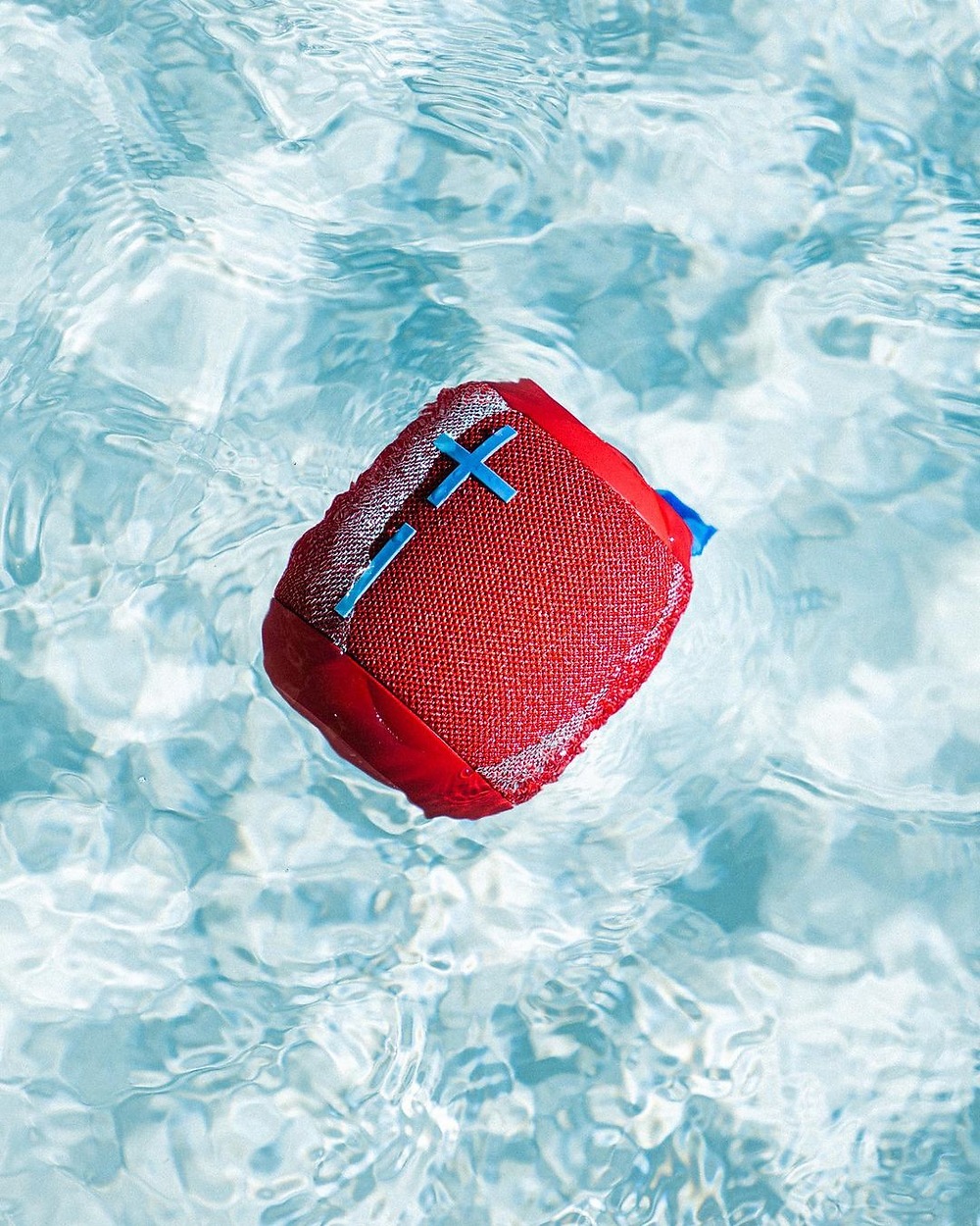 red bluetooth headphones floating in clear blue water