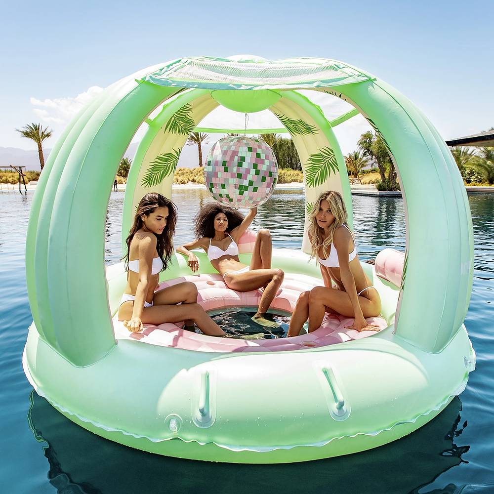 three adult woman on a green disco ball pool float on water