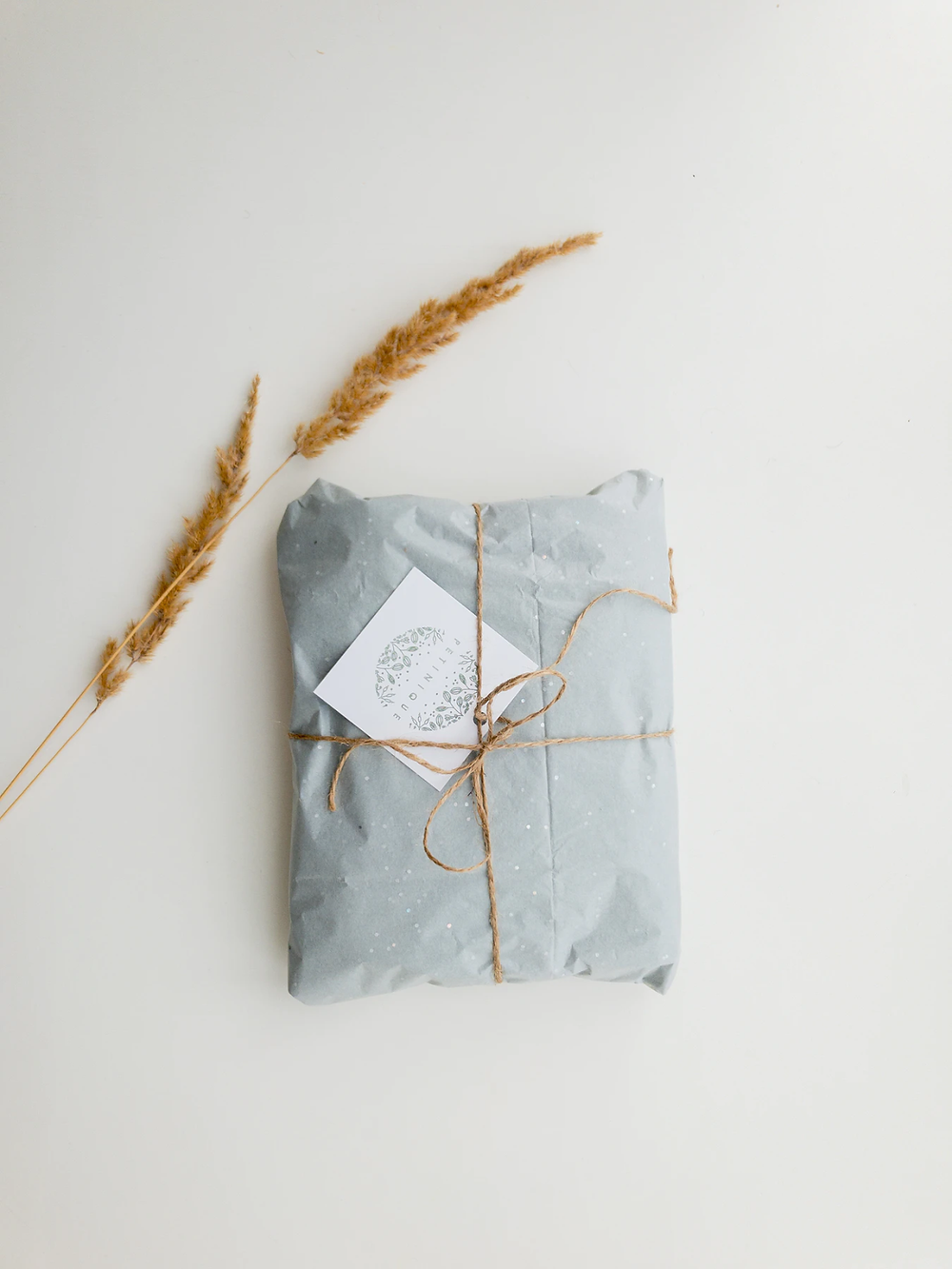 light blue parcel wrapped in twine with sprigs of wheat in the corner
