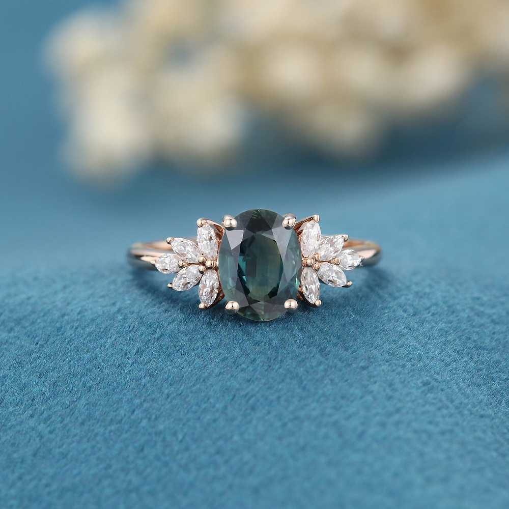 ring with blue stone and smaller diamonds on blue cloth unique engagement ring