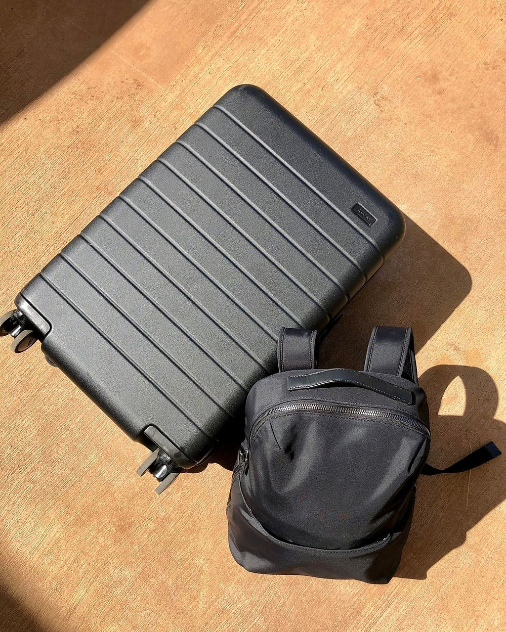 Away carry on suitcase and a small backpack