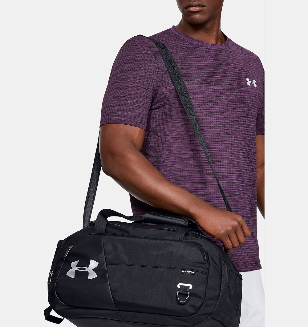 Man in purple Under Armor shirt with an Under Armor duffle bag