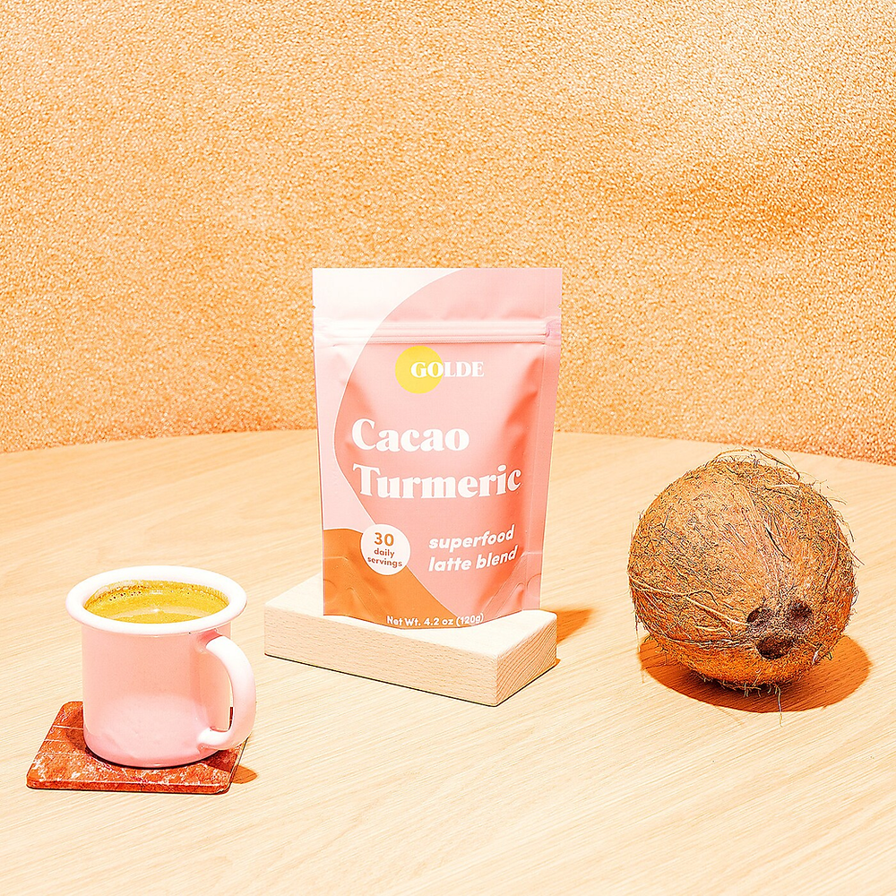 Golde Cacao Turmeric Latte blend for glowing skin on table with coconut