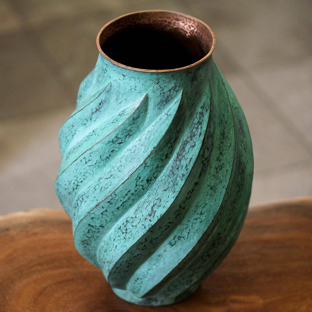 green copper vase with wave like ridges on a wooden table