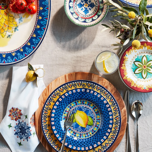 colorful blue and yellow dinnerware with lemon motif on olive wood plate charger on white linen tablecloth