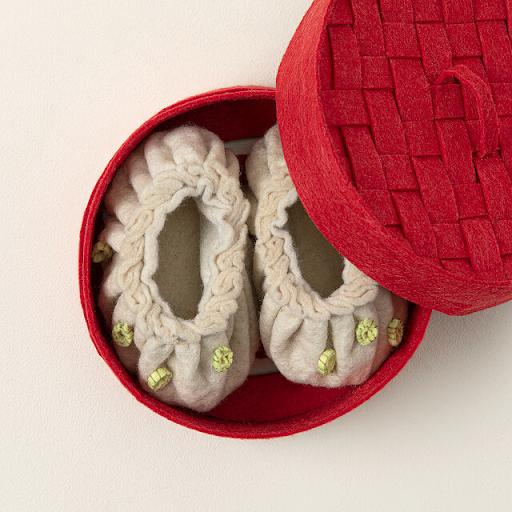 wool booties in the shape of dumplings in a steamer shaped red box
