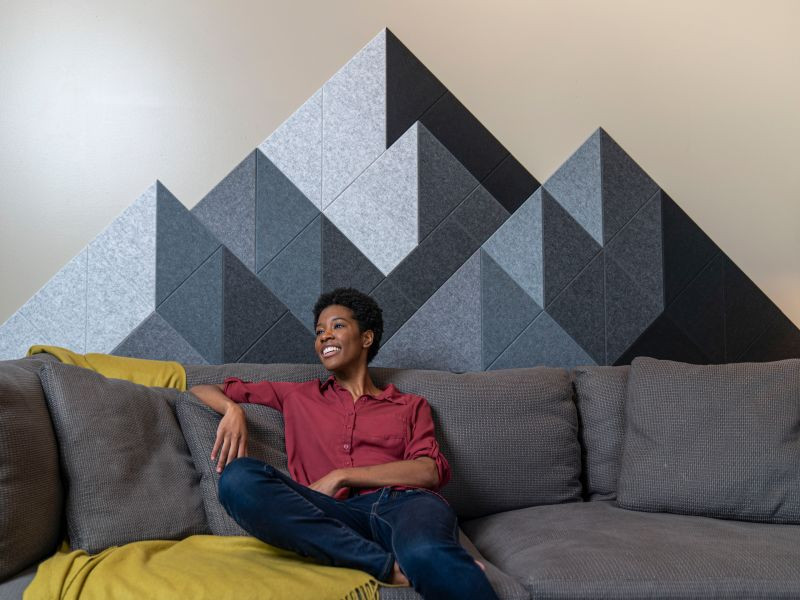 woman on grey couch with felt panels in the shape of a mountain behind her