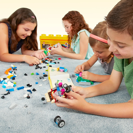 four children playing with lego pieces on a grey carpet