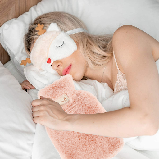 fluffy pink hot water bottle holder in the arms of a sleeping woman gifts for new mothers