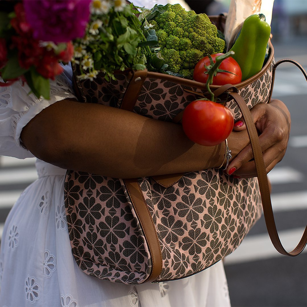 woman holding kate spade jacquard tote with vegetables in it