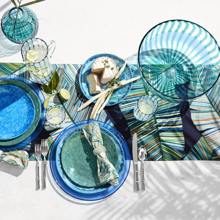 white table with blue and green palm table runner with blue and green dinnerware