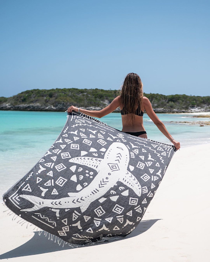 Woman holding large turkish towel with a boho themed shark design on the beach