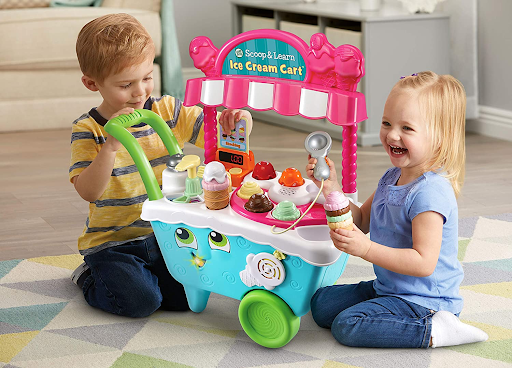 light blue and green ice cream truck toy with two children playing
