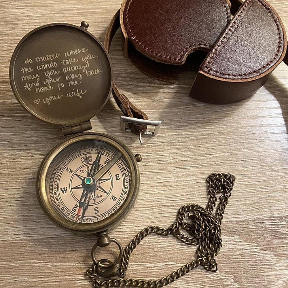 engraved compass with chain on table