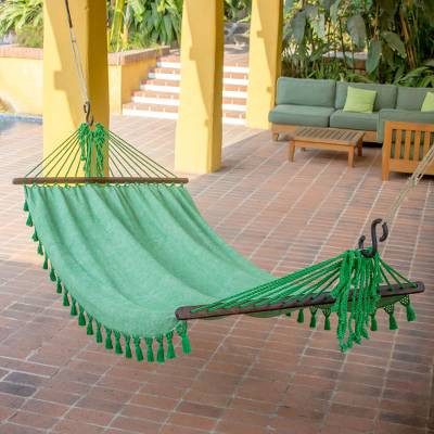green hammock with tassels hanging on a porch