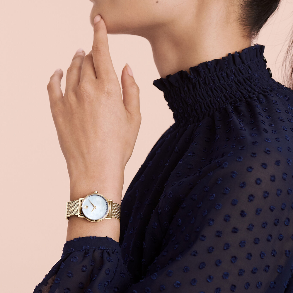 woman in a dark blue shirt with a movado watch on her wrist