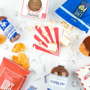scattered popcorn chips and other snacks on a table with red white and blue