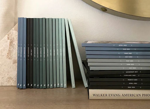 a series of monthly photo books in ombre shades of green on a table gifts for new moms